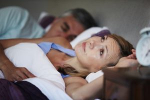 A woman lies awake unable to sleep