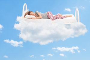A woman sleeps peacefully on a cloud.