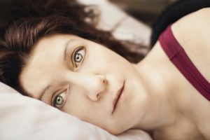 a woman lies awake suffering from sleep apnea